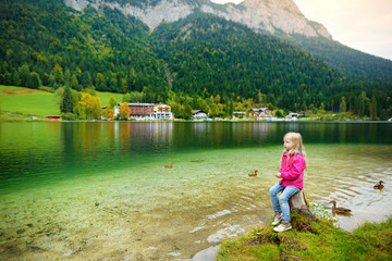 Fototapete - Cute little girl enjoying the view of wonderful green waters of Hintersee lake. Amazing autumn landscape of Bavarian Alps on the Austrian border, Germany.