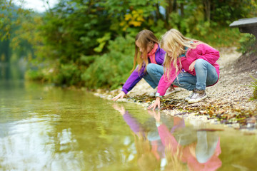 Fototapete - Two little girls enjoying the view of wonderful green waters of Hintersee lake. Amazing autumn landscape of Bavarian Alps on the Austrian border, Germany.