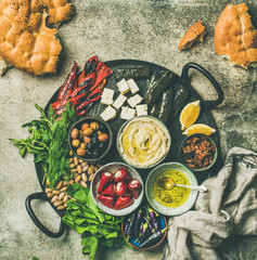 Mediterranean, Middle Eastern meze starters platter. Flat-lay of stuffed pickled paprikas, cheese, dolma, hummus, spiced oil, olives, sundried tomatoes, nuts, flatbread on tray, top view copy space