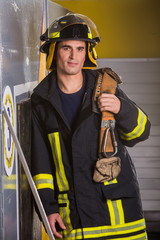 a tired fireman is standing with his belt in his hand leaning against the wall