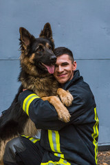 firefighter plays with a sheepdog, hugs, rejoices
