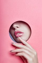 Beautiful girl with pink plump lips peeks out through a round hole in pink paper. Perfect lips and lipstick. Cosmetics, makeup, facial care, secret, hidden face, hand in front of lips