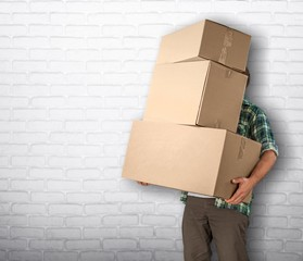 Man with cardboard boxes on brick background