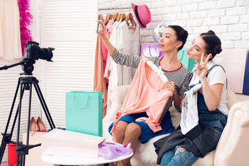 Two fashion blogger girls hold up two colorful dresses to camera taking selfie.