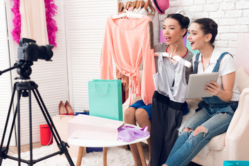 Two fashion blogger girls hold up colorful dresses and tablet to camera.
