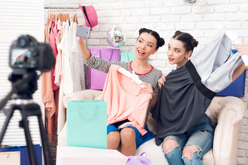 Two fashion blogger girls pull colorful dress from colorful bags to camera.