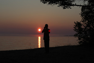 Man takes a photo on the smartphone of the setting sun over the lake baikal