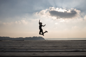 Enthusiastic woman jumping in air against sky