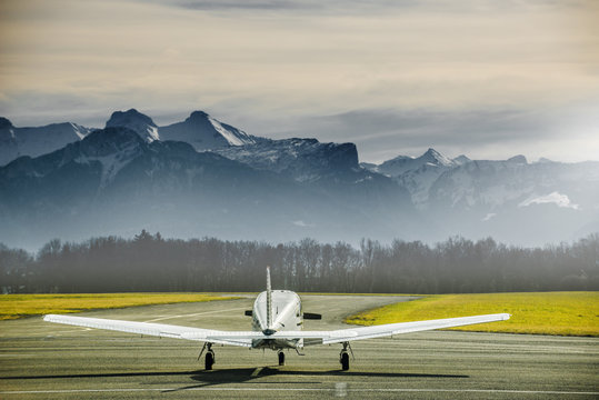 Propeller plane parking at the airport. Small airfield in front of high mountains. Sunset over mountains.