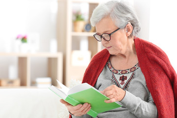 Mature woman with hearing aid reading book indoors
