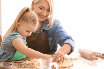 Little girl and her grandmother making cookies in kitchen