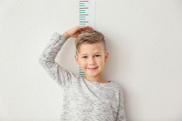 Cute little boy measuring height near light wall