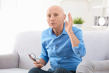 Senior man with hearing aid indoors