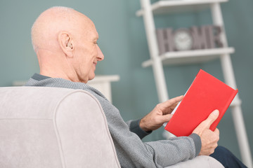 Senior man with hearing aid reading book indoors
