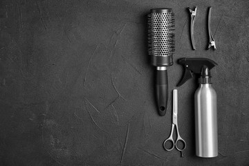 Flat lay composition with professional hairdresser tools on black background
