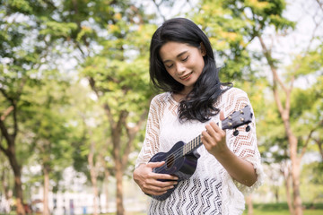 woman play on Ukulele in park