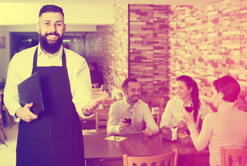 Waiter welcoming guests in restaurant
