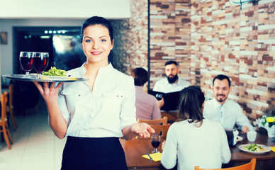 Young woman waiter greeting customers at