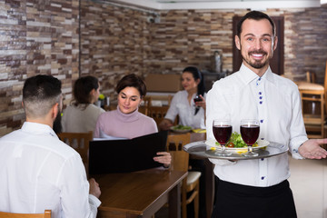 Portrait of adults in middle class restaurant and young waiter
