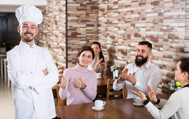 Cheerful chef listens to praise of the food