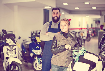 Worker with  woman customer in motorcycle workshop