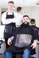 cheerful guy stylist demonstrating final haircut to client at hairdressing salon