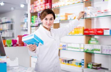 Happy female pharmacist suggesting useful drug