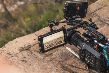 A professional camera is recording the view of a city. The viewfinder is open and showing different video parameters. The camera is placed upon a rock.