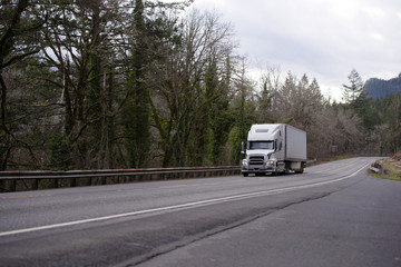 Modern big rig semi truck with refrigerator semi trailer driving with cargo by gorgeous Columbia Gorge winding road