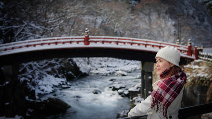 Woman in white coat standing on Shinkyo bridge that covered by snow during autumn and winter season, landmark in Nikko, Japan