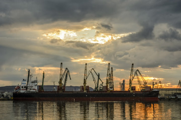 Boat waiting to be loaded with Cranes at sunset.