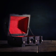 Image of empty mysterious treasure chest over wooden table.