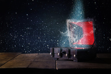 Image of mysterious treasure chest with glitter light and smoke over wooden old table.