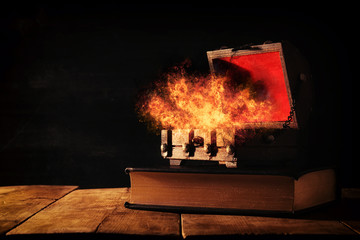 Image of mysterious treasure chest with flames over old book on wooden table.