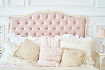Large buttoned headboard of luxury bed, beige and pink pillows on it, copy space. Feminine bedroom in pink and white colors. Chesterfield style checkered soft headboard, diamond pattern