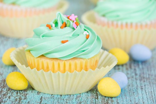 Easter spring cupcake with candy eggs and sprinkles on wooden green table