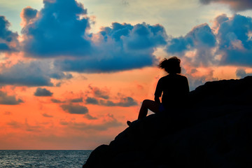 Woman silhouette at sunset. Girl sits on  rock above tropical sea. Evening sky of orange color with blue clouds. Landscape.