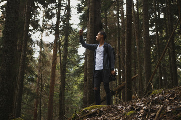 Young hipster guy taking photo on his mobile phone camera of a beautiful landscape while standing near lake, bearded man shoots video on cell telephone during amazing travel through the countryside