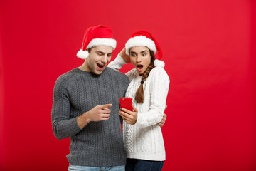 Christmas Concept - Young handsome and beautiful couple enjoy checking on mobile phone in christmas day