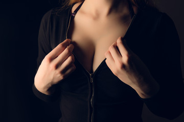 Sexy woman tits in black jacket. Woman zip up black jacket. Woman hands take zip lock of black sweater
