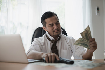 Asian Businessman looking money and holding a gun at office desk.