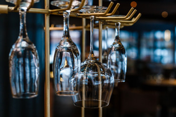 Empty glasses for wine above a bar rack in vintage tone.