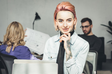 selective focus of smiling tattooed businesswoman at workplace with colleagues near by in office