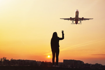 Girl wave to the plane with sunset background