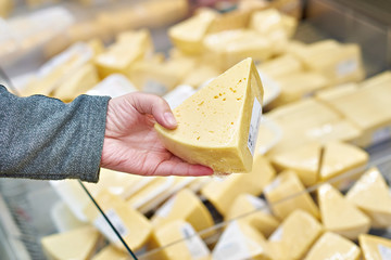 Hand buyer with piece of cheese in store