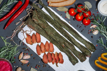 Delicious, smoked sausage on a dark wooden board with tomato and spices. Tasty snack handmade from natural ingredients.
