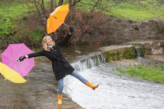 femme riant avec des parapluies sur une cascade d'eau