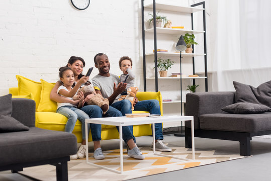 happy young family watching tv together at living room