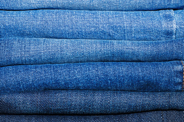 A stack of several classic jeans in a closet for clothes