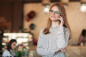 Blond Business lady with glasess use phone in cafe